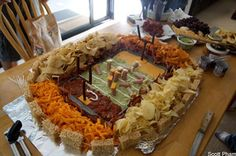 {Best Superbowl party food ever!!} The field is a sea of guacamole with cheese dip and salsa end zones. It's lined with sour cream for the yard markers and Slim Jim goal posts. Ruffles, tortilla chips, Cheetos and Doritos cheer on Vienna sausages with little cheese helmets while they play on the field, separated only by hotdogs and bacon. The stadium itself is created with rice crispy treats