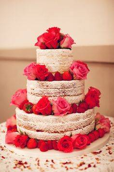 Unfrosted wedding cake adorned with fresh strawberries and red + pink roses. #food #wedding #cakes #roses