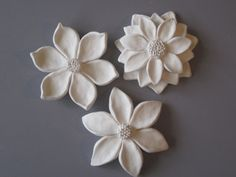 White Flower Bloom Wall Hanging    OOAK -Set of three flower bloom wall sculptures. Each flower is hand pinched from white clay, wet polished and kiln fired for a beautiful and durable snow white finish. Designed to grace a garden bath or shower these look great on any wall, over or between windows, along a beam or down a column. There is a hole in back for hanging and they are 4 to 5 in size. Each bloom is hand made and signed by me. Specifications:  Three flower blooms  size- varies from…