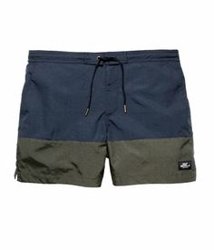 David Beckham Bodywear. Swim shorts with elasticized drawstring waistband. Side pockets, one back pocket with flap and fastener, and zip fly with Velcro fastener. Mesh liner shorts.