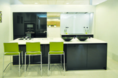 Hoogglans keuken met contrastkleuren. Deze moderne keuken heeft hoogglans keukenkasten die tevens ook greeploos zijn. De keuken is opgesteld met twee verschillende contrastkleuren .Het donkere van de keuken steekt mooi af op de heldere kleur van het werkblad in keramiek. De groene decoratie geeft de keuken een frisse en vrolijke toets.