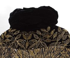 Detail of the beaded velvet and brocaded satin evening coat, c.1922. The shoulders, cuffs, and collar are of black velvet. The surface  is covered with gold beads and sequins.
