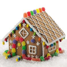 Such simply and charming beauty in this cottage decorated with icing lattice and snowflakes. Rooftop is lined with gum drops and a colorful pathway is trimmed with mini multi-colored candies.