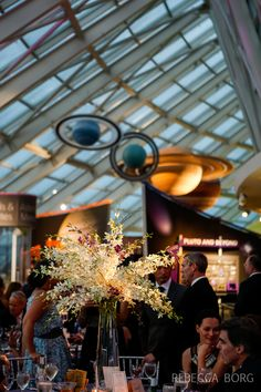 adler planetarium wedding in chicago illinois centerpiece with tall glass vase and flowers pouring out of it