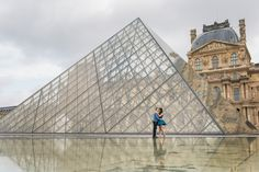 Kissing in Paris in front of the Louvre Pyramid. Engagement photo captured by Fran Boloni, engagement photographer at Kiss me in Paris