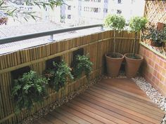 Balcony railing design with bamboo for privacy and to hang planters from. The rock border around the wood flooring gives this just the right finishing touch.