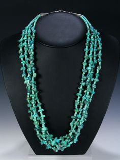 This beautiful necklace is made up of four strands of lovely turquoise nuggets and heishi beads with sterling silver beads and cones at the end. Finished with a
