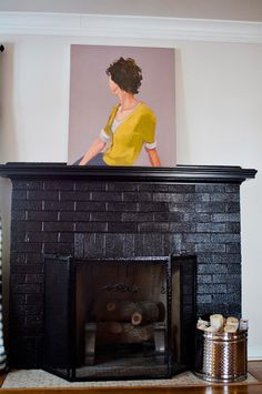 Painted brick fireplace. A glossy black helps cover the dated brick and mantle, but maintains a vintage style. Paint: Dark Kettle Black by Valspar
