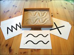 "This is a small sandbox. Uses pre-writing or teaching numbers/alphabet and shapes.   (Fine or Large Muscle Movement Sensory Activities) k4 Forms irregular, wavy lines and labels them ""writing"" or "" my name""."