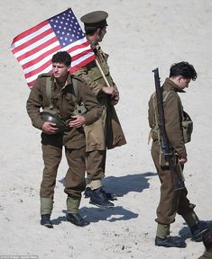 Looking the part: One the actors carries a US flag as he waits with fellow extras. http://www.dailymail.co.uk/tvshowbiz/article-3610394/325-extras-cardboard-cut-outs-line-beaches-recreate-World-War-II-evacuation-330-000-soldiers-epic-new-movie-Dunkirk.html