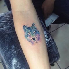 Watercolor wolf tattoo on the right inner forearm.