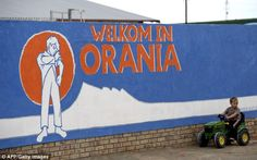 'Welkom in Orania' proclaims a mural, painted in white, blue and orange.  But this South African town, in the remote Northern Cape province, does not extend its welcome to everyone.  The colour scheme on the wall - accompanied by the community emblem of a boy pulling up his sleeves - harks back to the old apartheid flag.