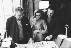 Honor Blackman with Producers Harry Saltzman and Cubby Broccoli looking at costume sketches for Pussy Galore.