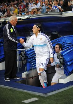 Mesut Ozil (R) of Real Madrid greets Real Madrid's pitch delegate Agustin Herrerin prior to the start of the la Liga match between Real Madrid CF and RC Deportivo La Coruna at the Santiago Bernabeu stadium on September 30, 2012 in Madrid, Spain.