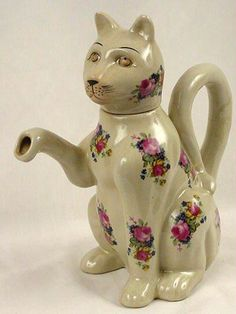 """white cat teapot, seated with raised paw as spout in style of Japanese maneki-neko (literally """"beckoning cat"""") lucky cat figures, decorated with pink rose bouquets, looping tail as handle, ceramic"""
