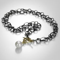 This John Iversen necklace is full of organic design coupled with a timeless appeal.  The double chain contains hammered oval links, hand-wrought in oxidized sterling silver.  At the front, a white freshwater pearl hangs from a decorative 18k yellow gold toggle clasp.  Dressed up or down, this necklace is a true work of art! @QUADRUM