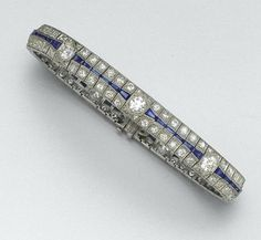DIAMOND AND SAPPHIRE BRACELET, CIRCA 1920 The articulated straightline set at intervals with 7 old European-cut diamonds, joined by segments of smaller old European-cut diamonds and calibré-cut sapphires, the total diamond weight approximately 7.50 carats, mounted in platinum, length 7½ inches.