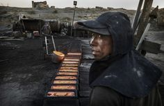 "In Inner Mongolia, China, a Chinese laborer pours molten steel at an unauthorized steel factory on November 3, 2016. To meet China's targets to slash emissions of carbon dioxide, authorities are pushing to shut down privately owned steel, coal, and other high-polluting factories scattered across rural areas. In many cases, factory owners say they pay informal ""fines"" to local inspectors and then re-open."