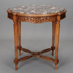 Dutch Carved Wood and Marble Side Table --- Turn of the century Dutch side table has a round marble table top and elaborately carved fruit wood apron with flowers, vines and interlocking circles. Reeded and tapered legs and medallion styled stretcher. Versatile size. ---  Item: 4904 --- Retail Price:  $2795