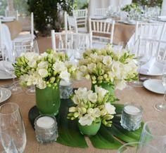 Centros de mesa con fresias blancas, en floreros verdes, manteles de arpillera y base de hojas de filodendro
