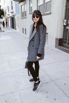 Comfortable #traveloutfit with a classic gray coat, black top, black jeans and black gym sneakers.