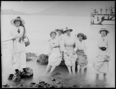 Group of unidentified women, paddling in the shallows [of a lake? sea inlet?], with people on a pier behind, probably Christchurch district