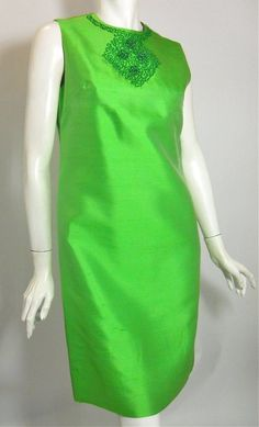 Emerald green silk 60s sheath dress with shimmering beads and rhinestones at neckline. Sleeveless, fully lined, back metal zipper. Has coordinating evening coat with pull-across tab that bottons to side, placket sculpted to reveal beading on dress when worn together. (without jacket)