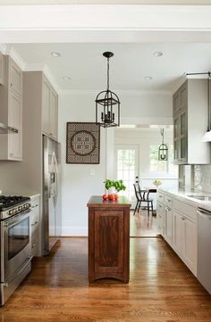 A small kitchen is no excuse for less storage -- a miniature kitchen island is right at home in this cottage space.