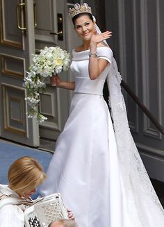 Crown Princess Victoria of Sweden wedding dress designed by Pär Engsheden.  It is made of cream-coloured duchess silk satin, with short sleeves and a turned-out collar, which follows the rounded neckline.  The train is edged with a border, fastened at the waist, and has the same shape as the veil. The train is almost five metres long.