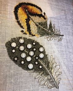 Pheasant and Guinea feathers. A darker version than I have done before, using dark grey beads, circled 'pearls' with black beads. I have used #tambourembroidery with gutermann sulky silver metallic thread which catches the light. . . . . . . . #embroidery