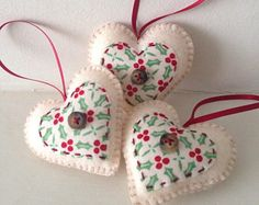 Set of three heart-shaped felt christmas decorations, with holly print appliqué.