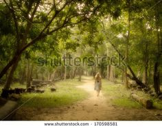 Young woman in dress walking barefoot on a mysterious path into an enchanted forest. - stock photo