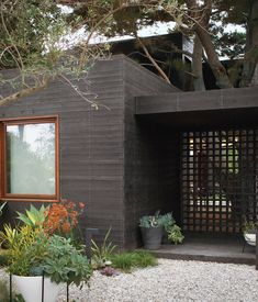 """The knotty cedar cladding from Crenshaw Lumber was pretreated with an ebony stain from Timber Pro UV—twice on both sides—prior to being brought to the site, where it was left for eight weeks so that it could adjust to the moist seaside air before installation. """"Cedar siding swells or shrinks when it gains or loses moisture while it reaches equilibrium with the content of the surrounding air,"""" says Michael. Photo by Coral von Zumwalt."""