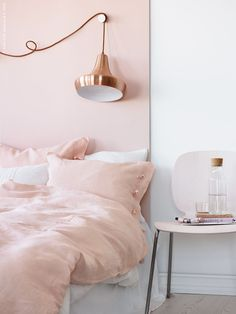 Sweet and chic. In this room, pink and copper complement each other perfectly. While the subtle tone of this particular pink softens the room, the metallic flash adds a touch of luxe. For this paint color pairing, choose Demure SW 6295 and Extra White SW 7006.