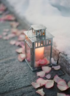 Gorgeous and simple decoration lining a path in a winter wedding. I love the soft pink rose petals and the candles in lanterns! <3