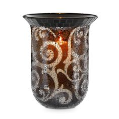 "Amaretto Large Hurricane   This dramatic statement piece presents stunning swirls of crushed artisan glass. Designed to sit on a flat surface, or use with our new Rustic Scroll Floor Stand, sold separately. Add a round pillar candle, or universal tealight tree to set the hurricane aglow. Includes leveling beads to stabilize pillar. 11""h, 9½""dia."