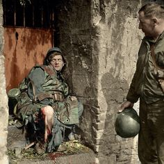 Coloured photo of a American GI looking at a dead soldat who bled out from taking a direct explosion hit to what looks like his leg.