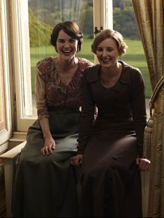 Michelle (Mary) and Laura (Edith), smiling and laughing behind the scenes on Downton Abbey.