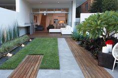 jardin compact avec un carré gazon et des allés en bois
