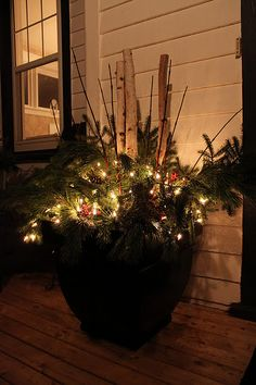Put lights in planter for lighting outdoors  OR solar lights with the greenery and tree branches!