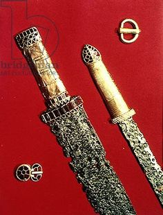Two swords with decorated hilts and two belt buckles, from the Pouan Treasure (gold, iron  garnet). Merovingian (5th century)