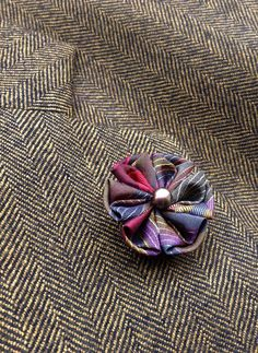 A muted jewel toned lapel flower for modern guys and women, made in the Japanese tsumami kanzashi style! I used a burgundy, purple, gold, green and gray vintage kimono silk to make this attention-grabbing lapel flower. I sewed a gray freshwater pearl into the center, and I mounted