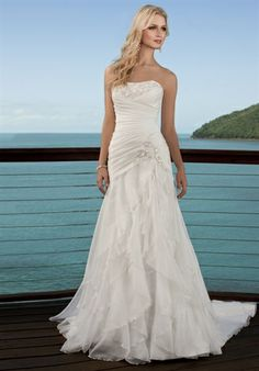 Make waves in this flowing, Soft Organza wedding gown with just the right touch of Diamante beading framing your neckline. Figure-flattering, sexy ruching throughout the bodice builds anticipation to the stunning asymmetrical skirt designed with tiered-layers of soft Organza. Concentrated beading accents add detail to the hip for a dramatic appearance.    Fabric: Soft Organza    Embellishments: Beading    Color: White, Ivory    Size: 2 - 20