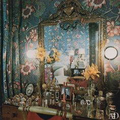 The bed, originally designed by Syrie Maugham, is reflected in a Louis XVI mirror over the dressing table. On the table are perfume bottles, family pictures and a photograph of Vreeland's late husband in a red-lacquered frame.