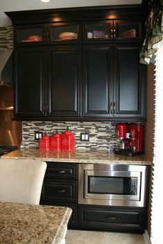 Love this! Dark cabinets, counters, backsplash.....red accents!! Yes please!!