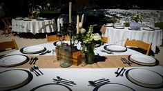 Wedding table top- vintage silver candle sticks, bottles, and mismatched silver place settings.