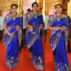 Blue uppada silk saree with silver zari border and colorful lotus flowers embellished zamdhani weave highlighted all over around the bord...