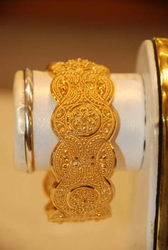 $2940.976, 21k  This design is most likely machine made and not with hand-stamping. Weight 55 gms. I don't see a screw-pin which is normal for this type of design