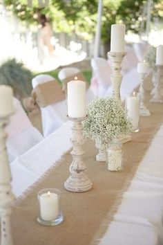 create drama with a burlap runner over a simple white table cloths and rustic candle holder centerpieces