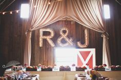 Marquee lights of couple's initials. Steel cutting done by a local high school shop class. Cafe lights from Target. Barn wedding. Rustic wedding. DIY. Barn wedding reception.
